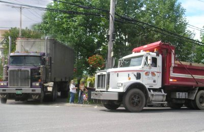 Mothers with strollers find themselves between huge trucks in what should be a peacfeull morning walk that suddenly is more like a monster truck show